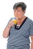 Senior woman drinking orange juice Royalty Free Stock Images