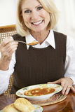 Senior Woman Drinking Soup Royalty Free Stock Image