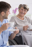 Senior woman drinking tea with her caregiver Royalty Free Stock Photo