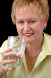Senior woman drinking water. A senior woman holding a glass of ice water Royalty Free Stock Photo
