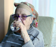 Senior woman drinking water. A senior woman with eyeglasses drinking water Stock Images