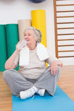 Senior woman drinking water on exercise mat Stock Photography