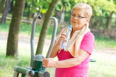 Senior woman drinking water after exercise on outdoor gym, healthy lifestyle Royalty Free Stock Image