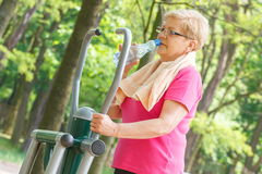 Senior woman drinking water after exercise on outdoor gym, healthy lifestyle Royalty Free Stock Photography