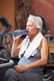 Senior woman drinking water in gym Stock Photo