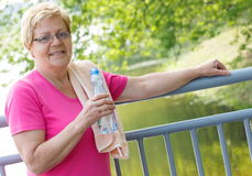 Senior woman drinking water and resting after exercise or running, healthy lifestyle Royalty Free Stock Photo
