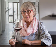 Senior woman drinking wine at a table Stock Photography