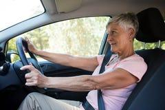 Senior woman driving a car. Active senior woman driving a car Stock Photos