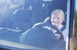 Senior woman driving car. Gray-haired senior woman driving car Royalty Free Stock Photos