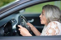 Senior woman driving car. Portrait of stressed senior woman driving car Stock Photos