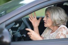 Senior woman driving car. Portrait of stressed senior woman driving car Royalty Free Stock Photography