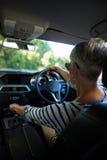 Senior woman driving car. Rear view of senior woman driving car Stock Images