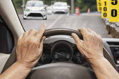 Senior woman driving a car on road. Royalty Free Stock Photography