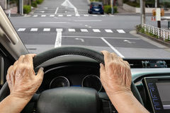 Senior woman driving a car on street in city. Senior woman driving a car slowly on street in city Royalty Free Stock Image