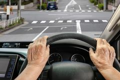 Senior woman driving a car on street in city. Senior woman driving a car on street in Tokyo Japan Royalty Free Stock Image