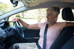 Senior woman driving a car. Thoughtful senior woman driving a car Royalty Free Stock Images