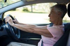 Senior woman driving a car. Thoughtful senior woman driving a car Royalty Free Stock Photography