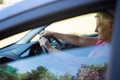 Senior woman driving a car. Thoughtful senior woman driving a car Royalty Free Stock Photos