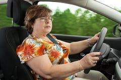 Senior Woman Driving a Car. Through the woods Stock Photos