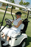 Senior woman driving golf cart