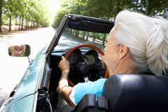 Senior woman driving in her sports car. Senior woman in sports car having fun Royalty Free Stock Images