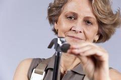Senior woman driving a nail Stock Image