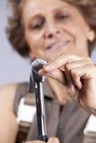 Senior woman driving a nail Royalty Free Stock Images