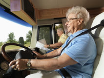 Senior woman driving RV. Senior adult woman driving RV and smiling while man reads map in passenger seat Stock Image
