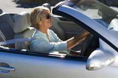 Senior woman driving silver convertible car, smiling, side view Stock Photo