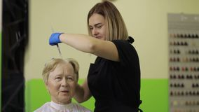 Senior woman dying hair at the beauty salon stock footage