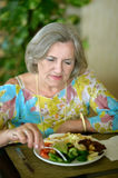Senior woman eating breakfast Stock Photos