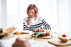 Senior woman eating breakfast at home. An old woman sitting at the table, reading a book Royalty Free Stock Photo
