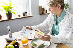 Senior Woman Eating Breakfast Reading Newspaper Concept stock images