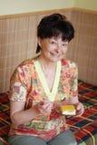 Senior woman eating cake Stock Photography