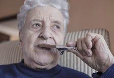 Senior woman eating a chocolate bar. A lovely senior woman eating a chocolate bar Royalty Free Stock Photography