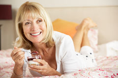 Senior Woman Eating Dessert In Bed Stock Images