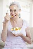 Senior Woman Eating Fresh Fruit Salad Stock Photography