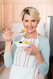 Senior woman eating fruit salad Royalty Free Stock Photos