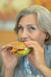 Senior woman eating hamburger Stock Photography