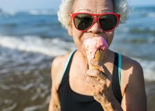Senior woman eating an ice-cream stock images