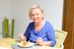 Senior woman eating a meal Stock Photography