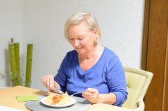 Senior woman eating a meal Royalty Free Stock Photography