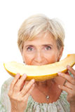 Senior woman eating melon stock images