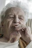 Senior woman eating something. Closeup of a senior woman eating something Stock Image