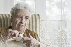 Senior woman eating something. A senior woman eating something Stock Images