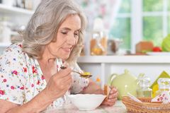 Senior woman eating soup. Senior woman sitting at kitchen table and eating soup Royalty Free Stock Photo