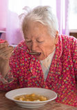 Senior woman eating soup Stock Images