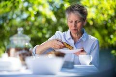 Senior woman eating sweet food in garden Royalty Free Stock Photos