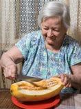 Senior woman eating yellow  melon. Portrait of senior woman eating yellow  melon at home Royalty Free Stock Photo