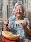 Senior woman eating yellow  melon. Portrait of senior woman eating yellow  melon at home Stock Image